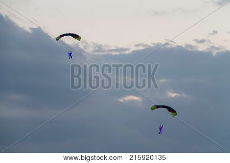 Two parachutists at an air show with lights