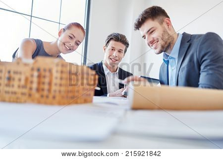 Business people planning in meeting with house draft