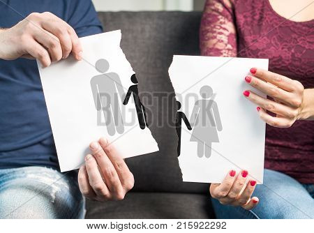 Break up divorce shared custody of children and breaking family apart concept. Bad parenting. Legal fight about kids. Couple ripping a paper with man woman and child icon.