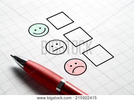 Customer satisfaction survey and questionnaire concept. Giving feedback with multiple choice form. Pen paper and emotion smiley face icons.