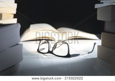 Glasses and open book on table surrounded by literature. Education learning and reading concept.