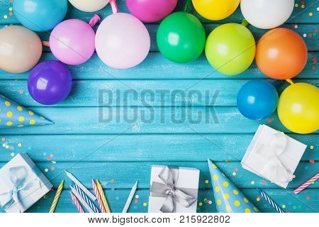 Holiday frame with colorful balloons gifts confetti and carnival cap on turquoise table top view. Birthday or party greeting card. Copy space.