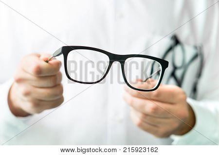Optician Holding Glasses. Eye Doctor Showing New Lenses.