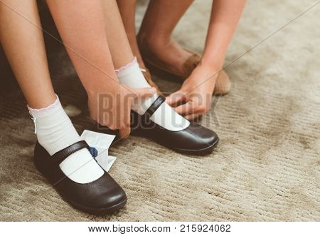 Mom Chooses Shoes For Her Daughter In The Store.