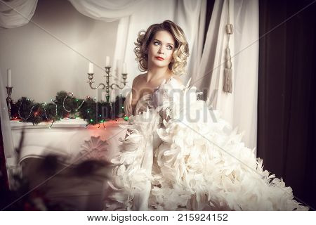 blonde in white feather boa. Horizontal frame on a light background