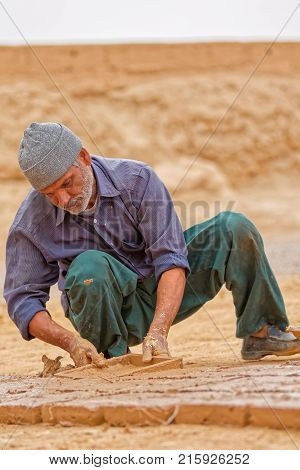 MEYBOD, IRAN - MAY 6, 2015: Man making the mud bricks in traditional way in Iran.