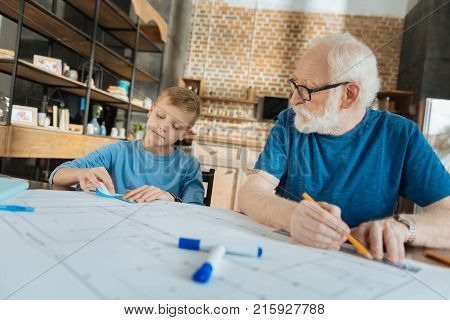 Engineering blueprint. Nice pleasant serious boy sitting together with his grandfather and helping with engineering blueprint while working together