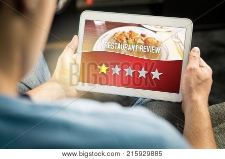Bad restaurant review. Disappointed and dissatisfied customer giving terrible rating with tablet on an imaginary criticism site application or website. Man giving one out of five stars at home.
