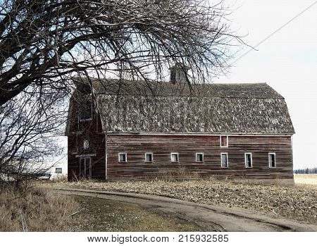 A black and white photo of a abandoned barn on a farmstead.