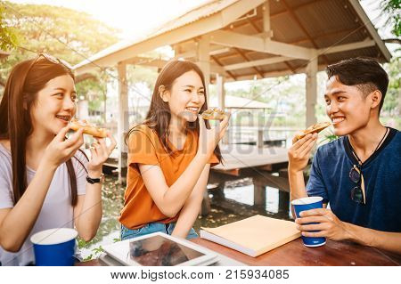 Asian students eating eating the pizza together in breaking time early next study class having fun and enjoy party Italian food slice with cheese delicious at university outdoor.