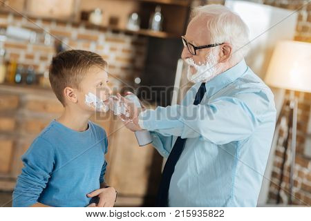 Male activity. Happy positive senior man looking at his grandchild and applying shaving foam on his cheeks while teaching him to shave