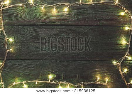 Photo of New Year's wooden green background with burning garland around perimeter.
