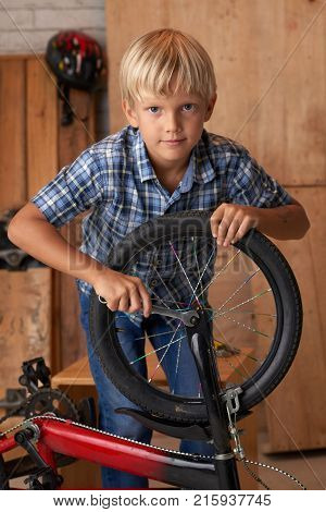 Boy tightening the screw of the front wheel of his bicycle