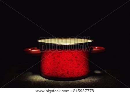 One old red cooking pot in the dark accentuated shape and texture.