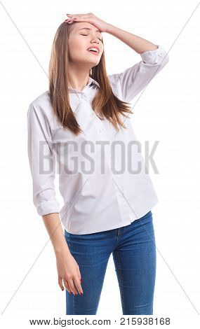 A young girl with beautiful hair in a white shirt with closed eyes is holding her hand on the forehead on a white isolated background