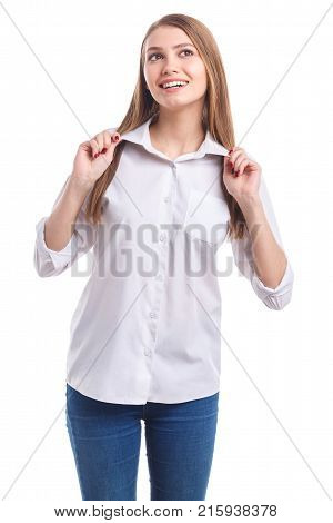 Young girl, with beautiful hair and smile holding on to the collar with both hands and looking to the side on white isolated background
