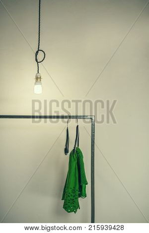 Glowing electric light bulb above the clothes hanger .  Green dress on the hanger under light bulbs. Light bulb on the wall background