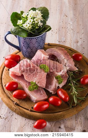 Three Pork Filets On Chopping Board With Herbs And Tomatoes