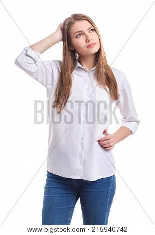 A young and thoughtful girl in a white shirt. Holds a hand on the back of the neck and on her side on a white isolated background