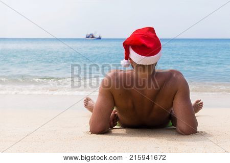 Man In Santa Claus Red Hat Sits On The Beach In Morning Hangover Christmas Holiday Party Dreams