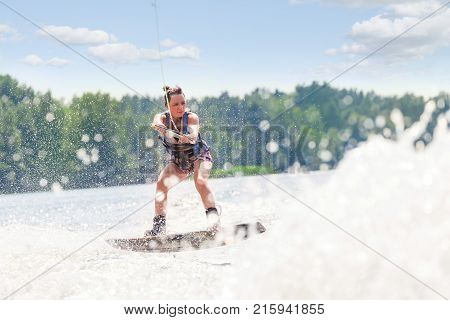 Young Pretty Slim Brunette Woman Riding Wakeboard On Wave Of Motorboat In Summer Lake