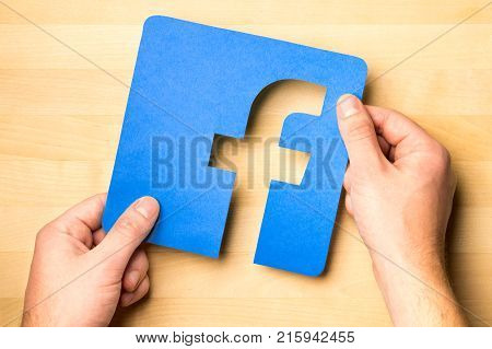 JYVASKYLA FINLAND - OCTOBER 7 2017: Hands holding Facebook logo cut from cardboard paper against wooden table. Facebook is a popular social media platform launched in 2004. Illustrative editorial.