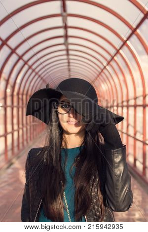 brunette girl in wide-brimmed hat standing in profile elevated pedestrian crossing with arches