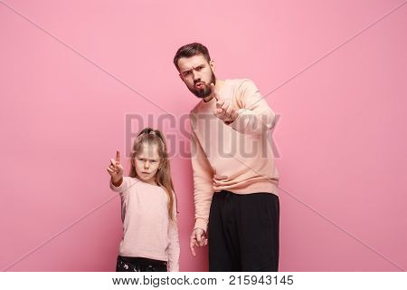 Young father with his baby daughter with angry, condemning and indignant emotions at studio pink background