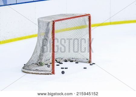 an ice hockey net withsome black  puck