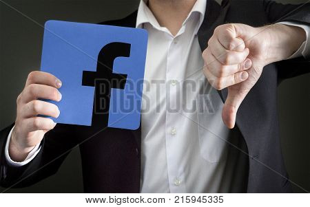 JYVASKYLA FINLAND - JUNE 13 2017: Man in a suit giving thumbs down with a cardboard Facebook logo. Facebook is a popular social media platform launched in 2004. Illustrative editorial.