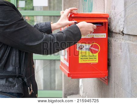WARSAW POLAND - MAY 24 2017: A tourist sending postcard. In Warsaw the mailboxes can be recognized by their bright red color.