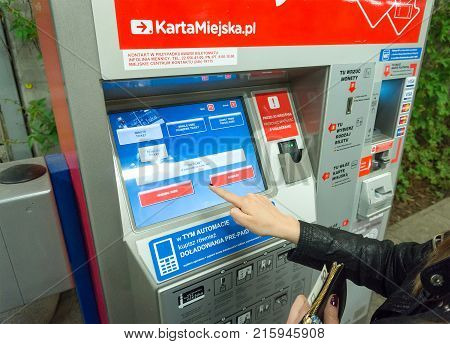 WARSAW POLAND - MAY 22 2017: Woman buying public transportation tickets from machine in Warsaw. Public transportation in Warsaw consists of tram train bus and subway.