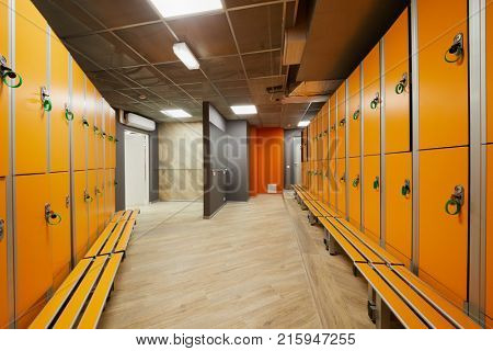 Rows of orange lockers and benches in the locker room.