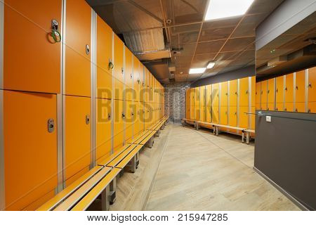Locker room with orange lockers at fitness center.