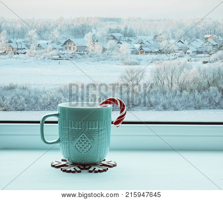 Winter still life - cup with candy cane on windowsill and winter landscape outdoors. Cozy winter still life with concept of spending winter time indoors. Winter composition. Winter background with Christmas winter mood