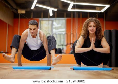 Man and woman in yoga positions on mats in gym.