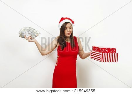 Young disconfused frustrated woman in red dress and Christmas hat holding gift boxes and money banknotes on white background. Santa girl with present and cash isolated. New Year holiday 2018 concept.