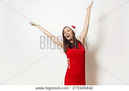 Pretty caucasian young happy woman with charming smile wearing red dress and Christmas hat spreading hands isolated on white background. Santa girl. New Year-2018 holiday. Copy space for advertisement