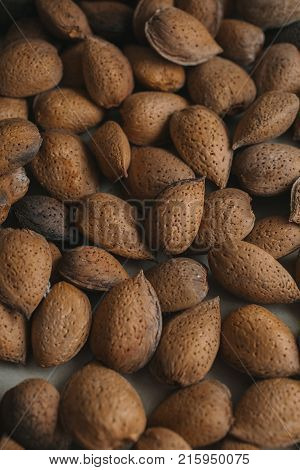 Shelled almonds as background. Close up view of shelled almonds texture and background for designers. Heap of almonds as background. Macro view of shelled almond. Almonds in their shells.
