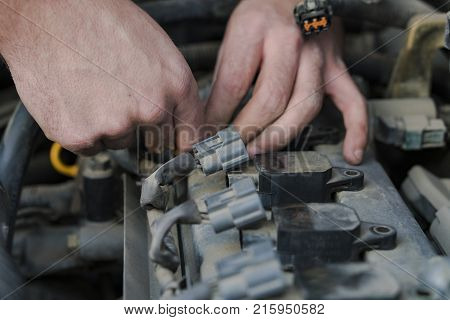 Car repair. An auto mechanic turns off the power to the spark plugs. Repair of the old machine.
