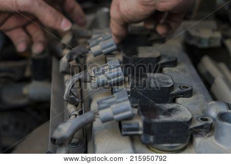 Repair avto.Ruki auto mechanic cut off the power of the spark plugs.