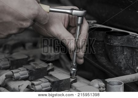 Checking the ignition system is finished. The key wrench in the hand of the auto mechanic. Work on fixing candles. Repair of the old machine.