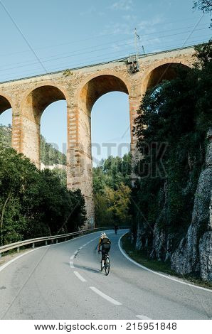 Teammates from cycling club ride together on beautiful quiet spanish countryside road under old Aqueduct bridge. Explore new landscape by training endurance