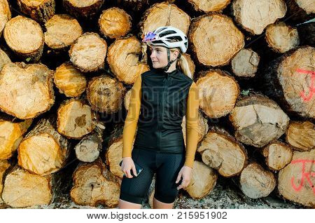 Cute female strong professional cyclist posing in all black lycra clothing jersey and vest stands on colorful background in front of cut and stacked logs early fall morning