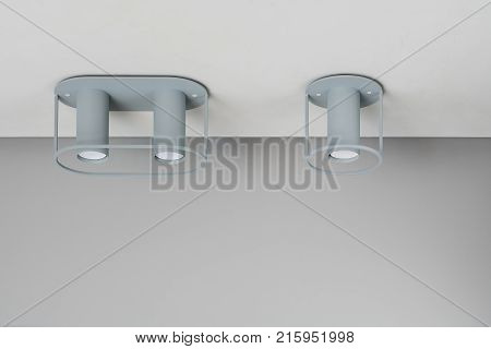 Two metallic gray lamps on the light ceiling indoors. One of them is double. Closeup horizontal photo.