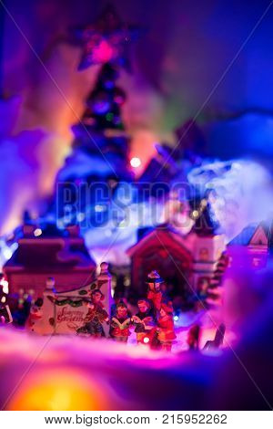 Seasons greeting with kids singing gospel with colorful Christmas village blurred in the background. Holiday festive miniature