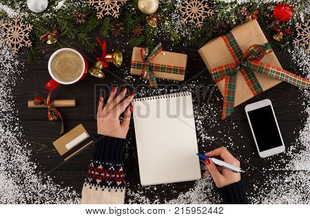 Holiday decorations and notebook with Christmas wishlist on rustic wooden table sprinkled with snow, with copy space, flat lay style. Top view, preparing for winter holidays concept.