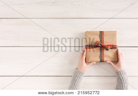 Gift wrapping background. Female hands holding handmade present box in craft paper and checkered bow at white wooden table background. Bithday or christmas preparation concept, top view, copy space
