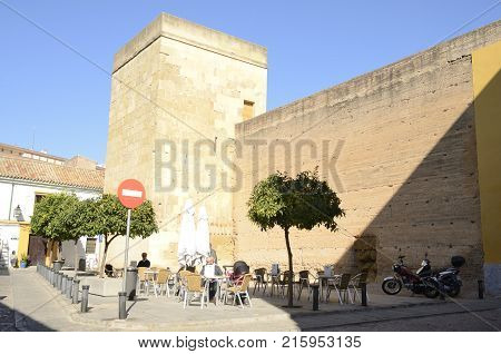 CORDOBA, SPAIN - NOVEMBER 19, 2017: Urban scene at bar terrace outdoor next to historic wall in the old town of Cordoba Andalusia Spain.