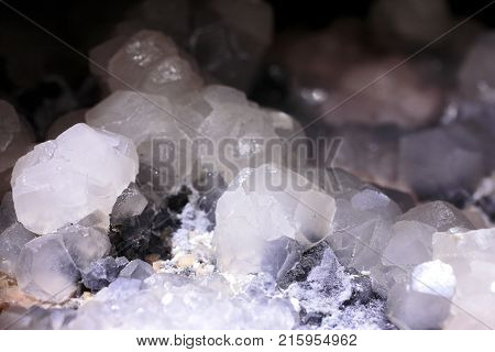 Closeup photograph of glittering translucent calcite stone crystal with purple, black and brown details with small black background. Natural phenomenon.